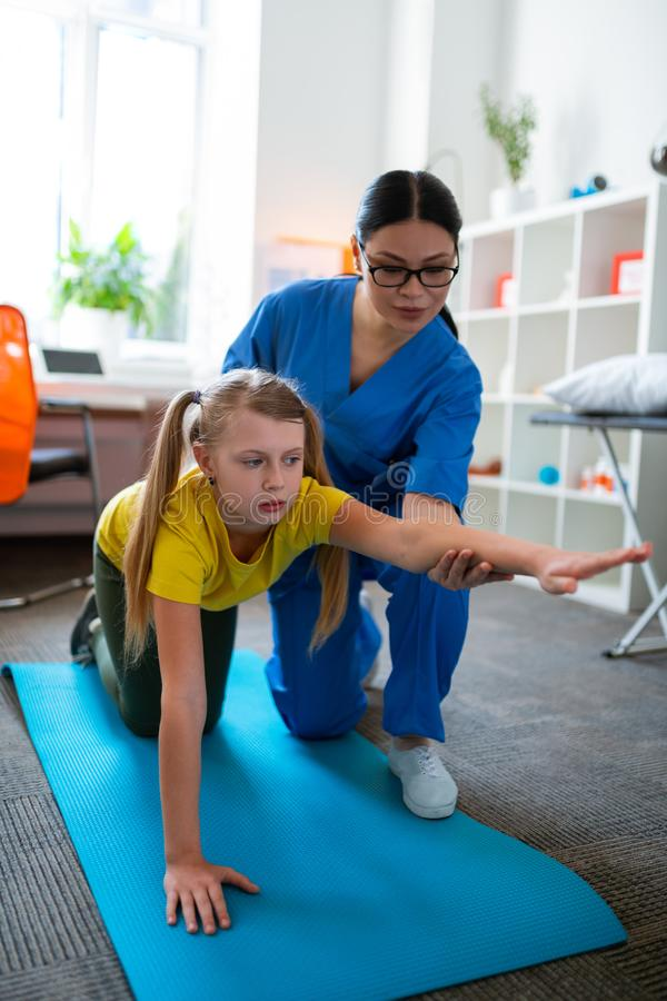 Ijverig licht-haired meisje die op blauw mat en het uitrekken zich lichaam blijven stock afbeelding