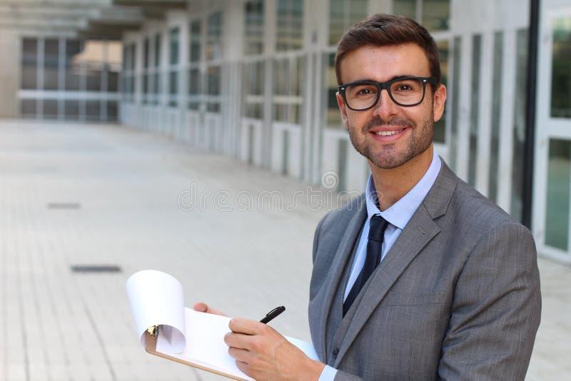 Ijverig mannetje die nota's in bureauruimte nemen stock fotografie