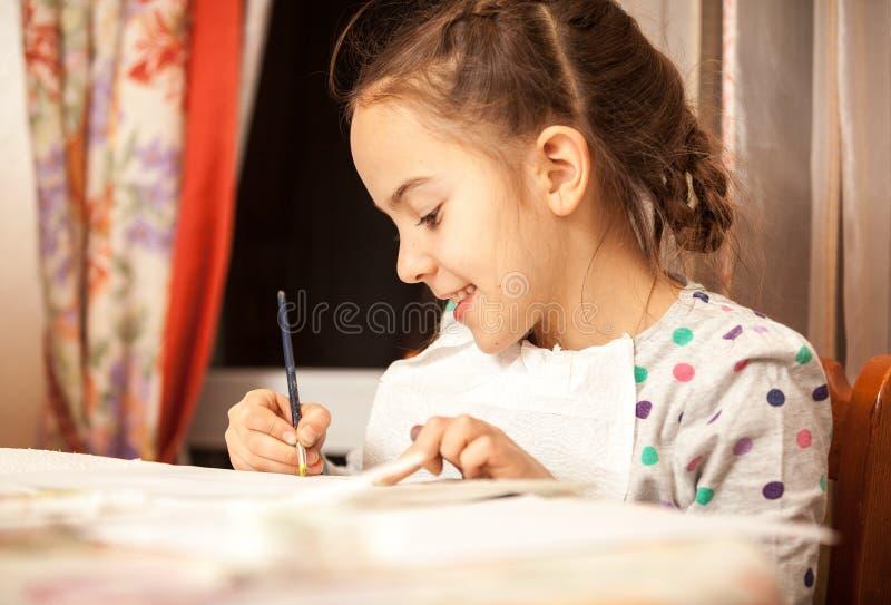 Ijverig meisje die tekeningen met borstel doen royalty-vrije stock foto