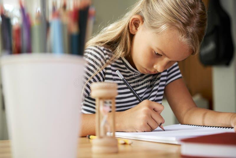 Ijverig schoolmeisje dat thuiswerk doet stock foto's