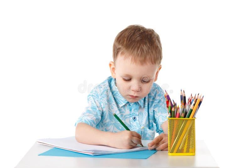 Ijverig trekt weinig jongen met kleurpotloden stock foto