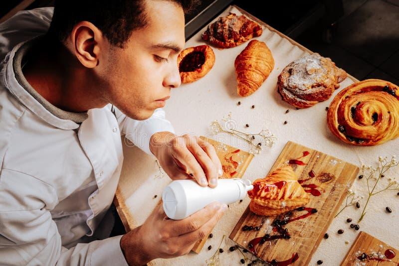 Ijverige jonge bakker die blij terwijl het verfraaien van gebakje voelen stock afbeeldingen