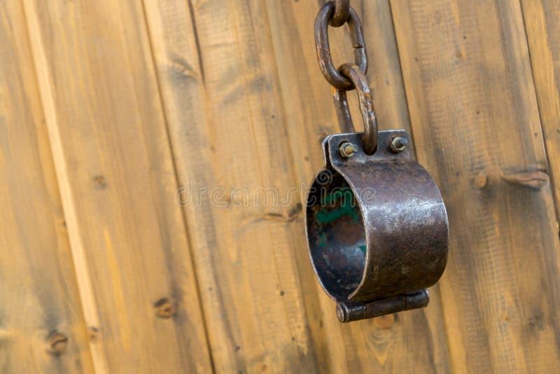 Ijzer oude kettingen met een ketting van geketende slaven en misdadigers middeleeuwse 1600 1800 handcuffs op een houten achtergro royalty-vrije stock foto's