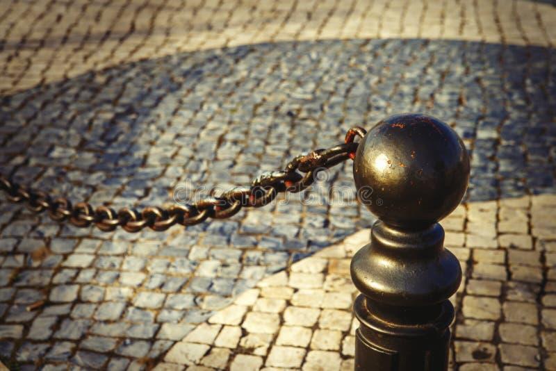 Ijzer oude pijler met ketting op de stoep dichtbij de weg stock afbeelding