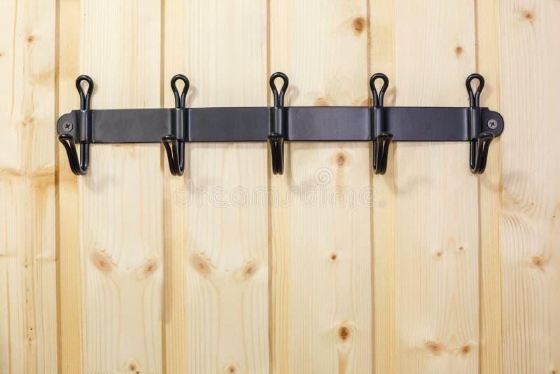 Ijzer zwarte haken voor kleren op houten muur royalty-vrije stock foto's