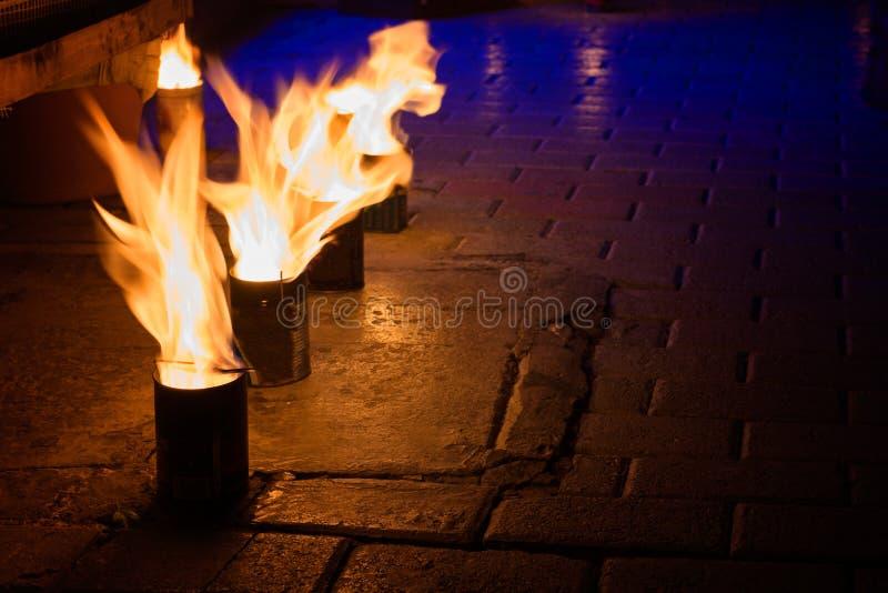 Ijzerblikken met het branden van vlammen op natte stoep op de straat royalty-vrije stock foto