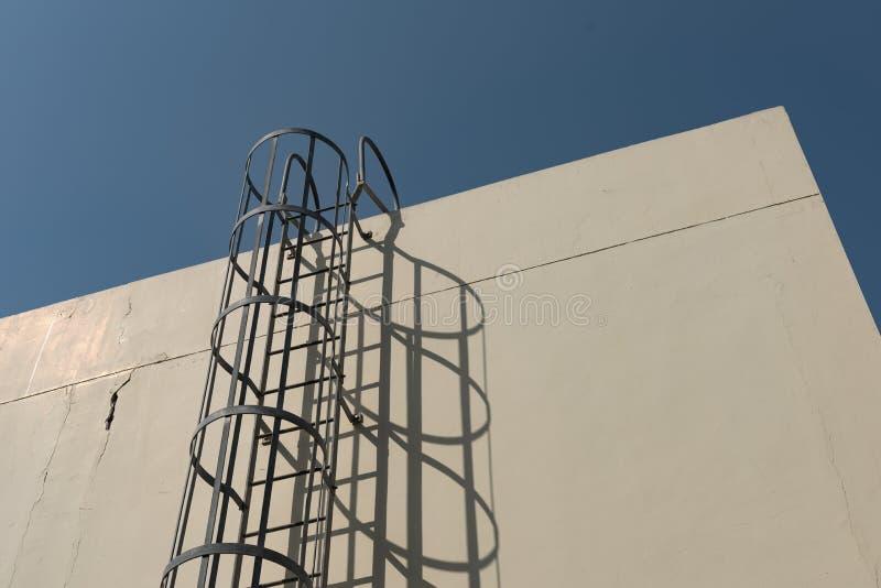 Ijzerladder in kooi aan de bouw van dakbovenkant royalty-vrije stock afbeelding