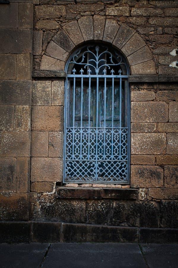 Ijzertraliewerk over oud overspannen venster royalty-vrije stock fotografie
