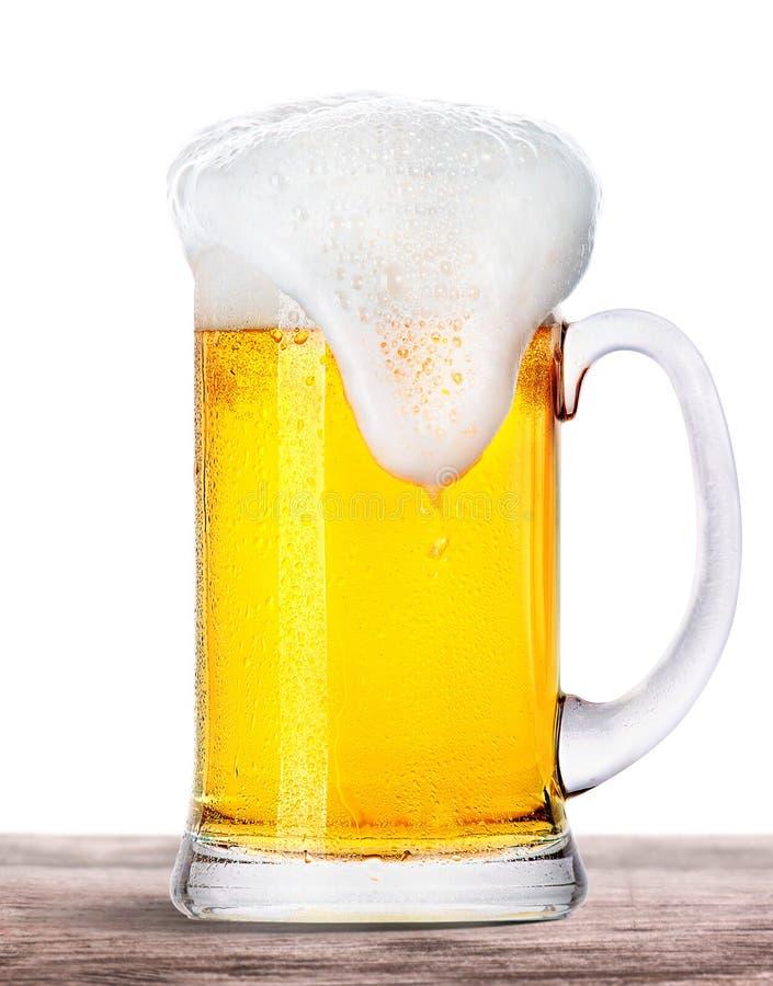 Ijzig die bier met schuim op houten lijst wordt geïsoleerd stock fotografie