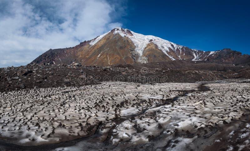 Ijzige gletsjers op de hellingen van Tolbachik-Vulkaan die over een gebied met sneeuw worden bekeken die met zand en as wordt beh stock fotografie