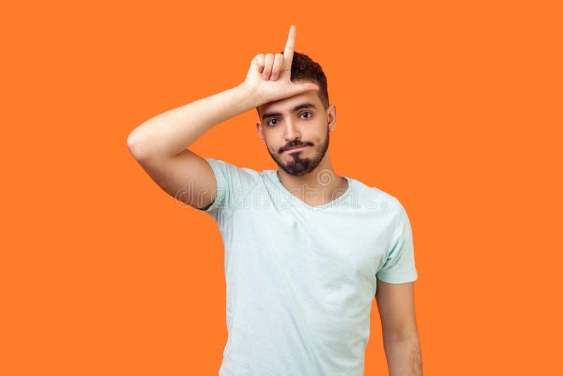 Ik ben loser. Portret van een ongelukkige brunette man met een loser gebaar, overstuur over de nederlaag studio ' s binnenshuis , stock afbeeldingen