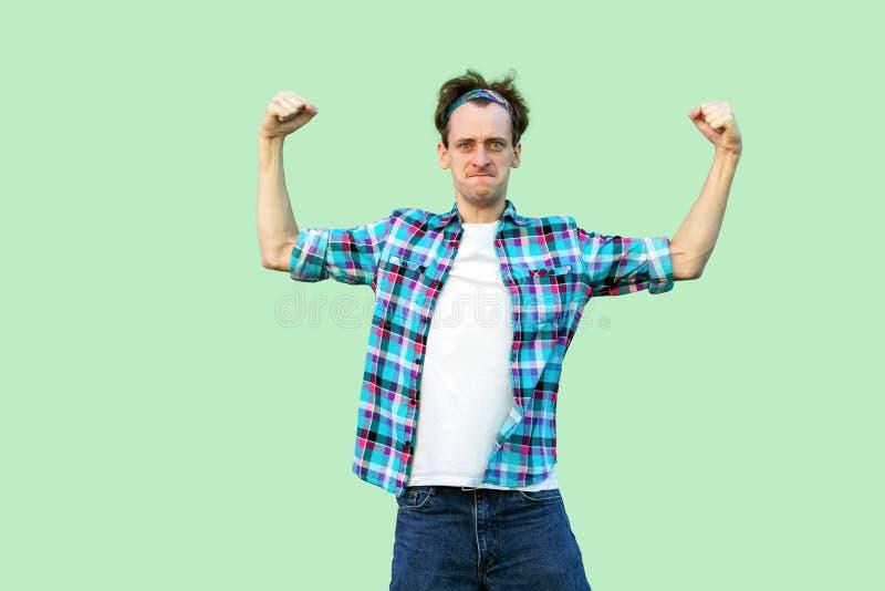 Ik ben sterk en onafhankelijk Portret van de grappige jonge mens in toevallig blauw geruit overhemd, hoofdband die zich met sterk stock foto