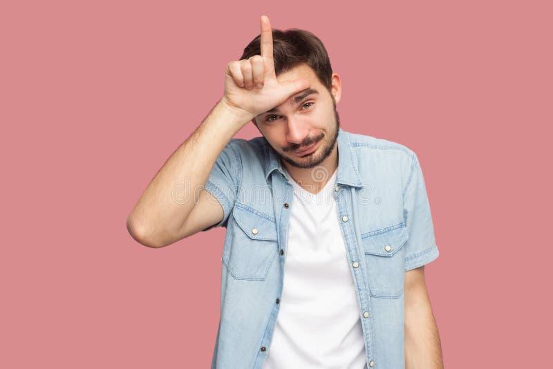 Ik ben verliezer Portret van de alleen gebaarde jonge mens in blauw toevallig stijloverhemd die zich met verliezersteken bevinden stock foto