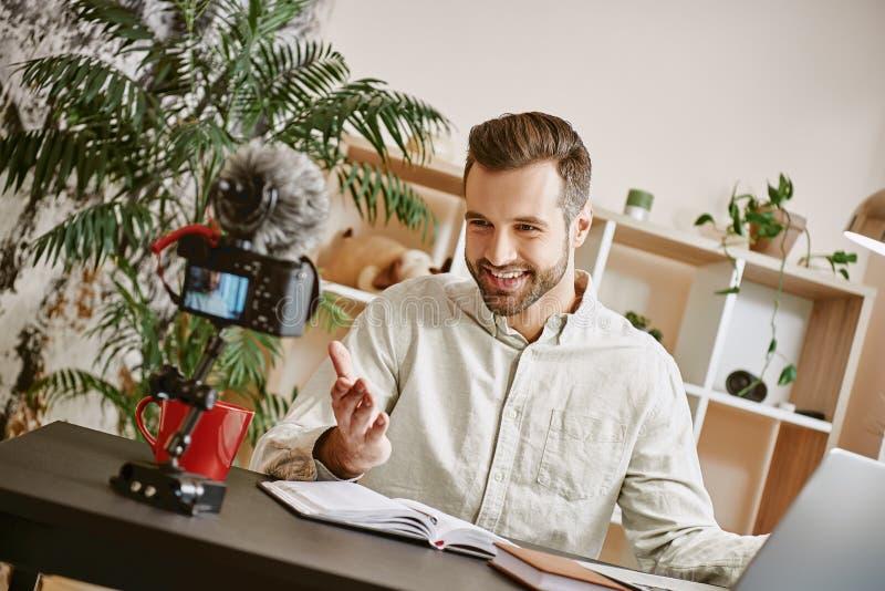 Ik ben zo gelukkig! Het vrolijke jonge mannetje die blogger een nieuwe inhoud voor zijn vlog met driepoot maken zette digitale ca royalty-vrije stock afbeelding