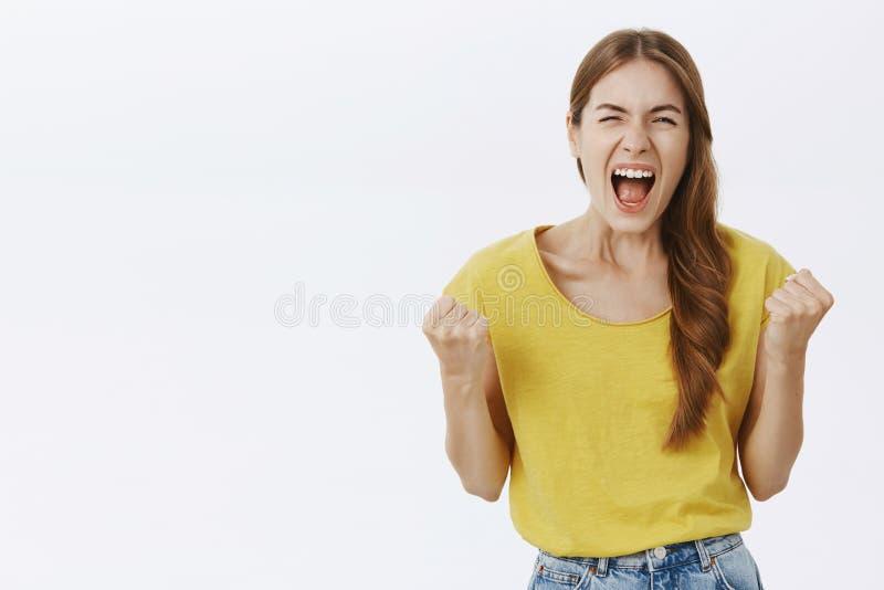 Ik haat u allen Portret van vrouwen verliezende bui die gek en zich verachtelijk in gele t-shirt die vuisten van woede dichtklemm royalty-vrije stock afbeelding