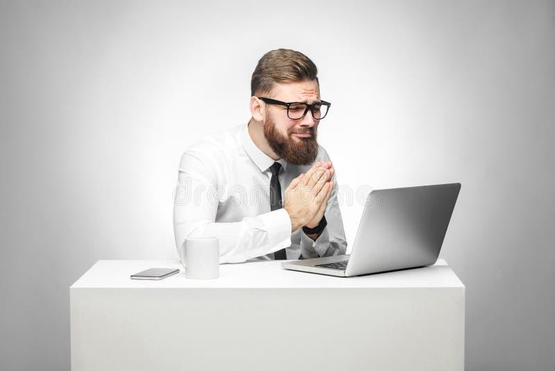 Ik heb uw hulp nodig! Het portret van hoopvolle gebaarde jonge manager in wit overhemd en de avondkleding zitten in bureau en spr royalty-vrije stock afbeeldingen