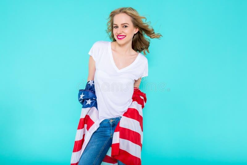 Ik houd van Amerika Gelukkige jonge glimlachende vrouw in jeans en witte T-shirt die Amerikaanse vlag houden en camera bekijken royalty-vrije stock fotografie