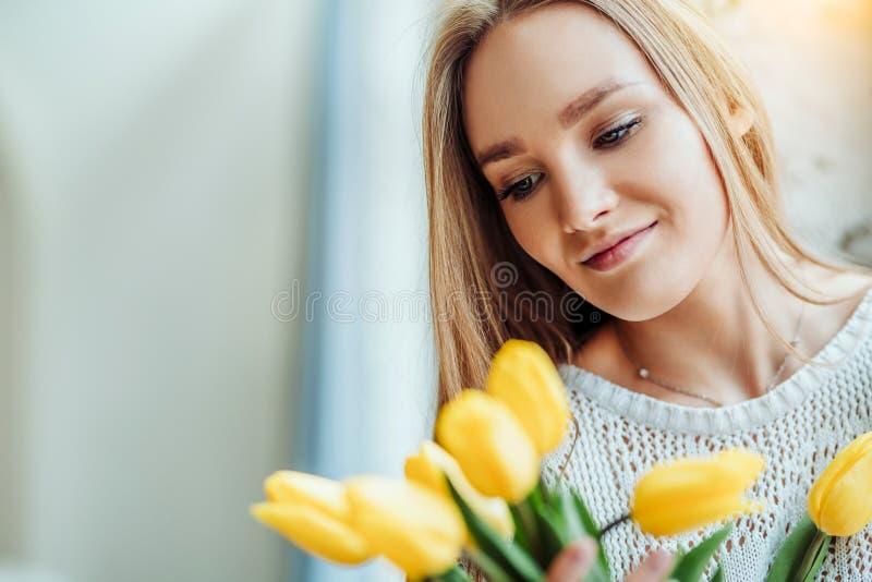 Ik houd van bloemen! Portret van mooie vrouw met boeket van gele tulpen stock afbeeldingen