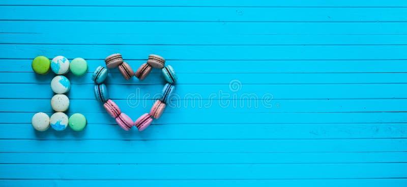 Ik houd van - multicolored makarons in de vorm van harten en de bekentenissen van minnaars liggen op een blauwe houten achtergron royalty-vrije stock afbeelding