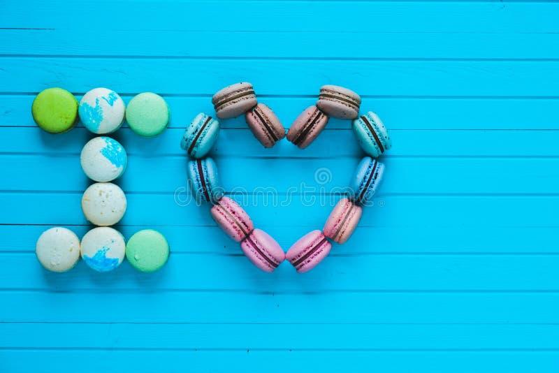 Ik houd van - multicolored makarons in de vorm van harten en de bekentenissen van minnaars liggen op een turkooise houten achterg royalty-vrije stock afbeeldingen