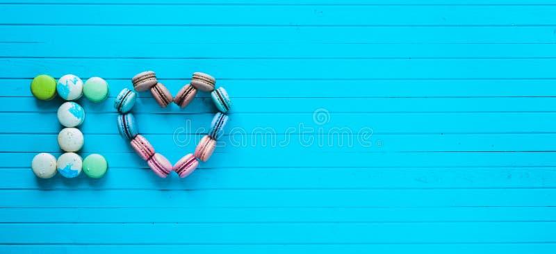 Ik houd van - multicolored makarons in de vorm van harten en de bekentenissen van minnaars liggen op een turkooise houten achterg stock afbeelding