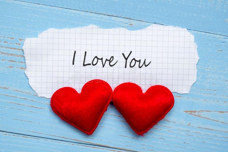 Ik HOUD van U verwoord op document nota met de vormdecoratie van het paar rode hart op blauwe houten lijstachtergrond Huwelijk, R stock afbeelding