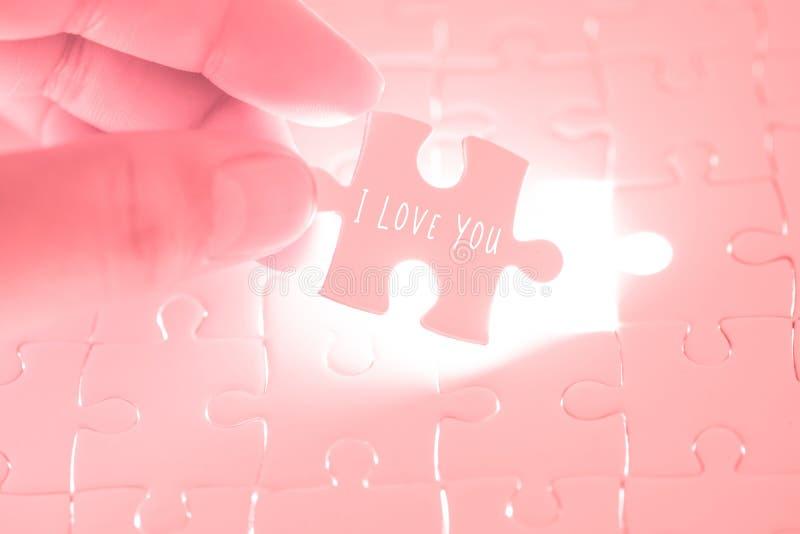 Ik houd van u verwoord op roze puzzel die holding door de handen zijn stock foto