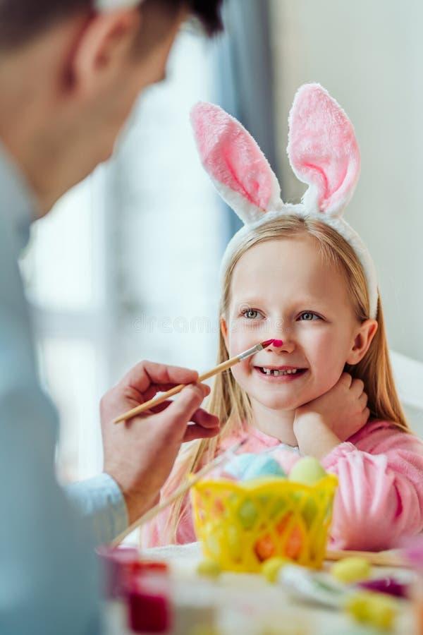 Ik houd van voorbereidingen treffend voor Pasen met mijn dadDad en de dochter heeft pret De papa schildert de neus van zijn docht royalty-vrije stock afbeeldingen