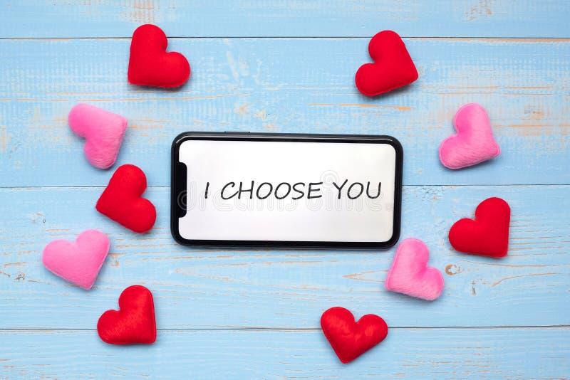 Ik KIES U op witte touchscreen vertoning van zwarte smartphone met de rode en roze decoratie van de hartenvorm op blauwe houten l stock foto