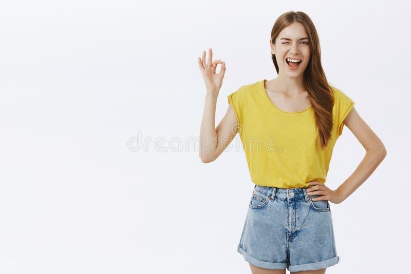 Ik kreeg alles onder controle Vriendschappelijk charmant Kaukasisch meisje in gele t-shirt en borrels die hand op heup houden royalty-vrije stock afbeeldingen