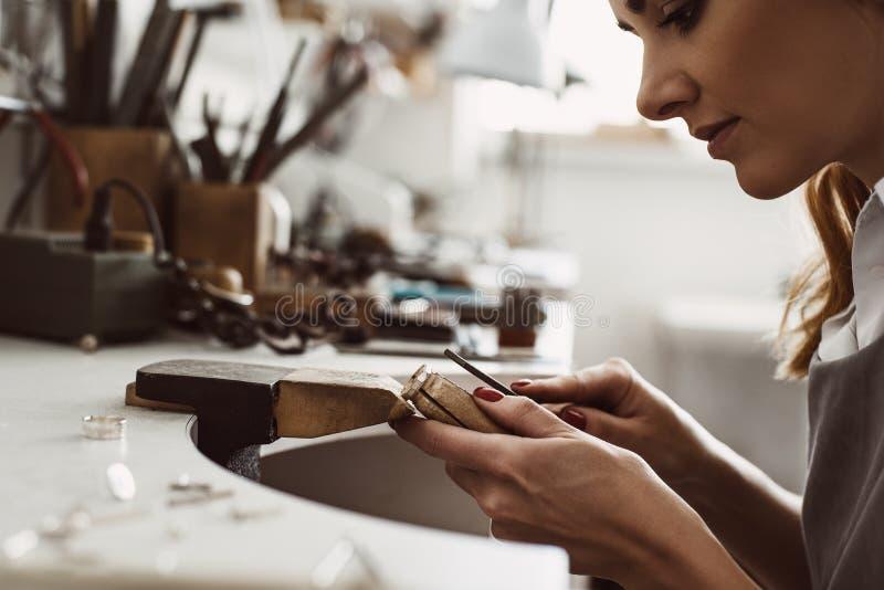 Ik kreeg mijn inspiratie Zijaanzicht van een vrouwelijke opgewekte juwelier die tot een zilveren ring leiden bij haar werkbank He royalty-vrije stock afbeelding