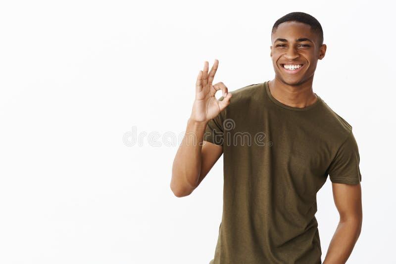 Ik kreeg u behandeld babe Charismatische knappe en zekere jonge Afrikaanse mens in het toevallige t-shirt flirty glimlachen en stock foto's