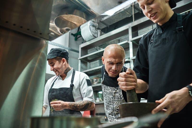 Ik let op u Strikte chef-kok die in schort zorgvuldig hoe zijn medewerker die restaurantkeuken werken bekijken stock afbeeldingen