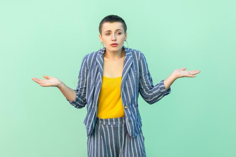 Ik trek `t het weet aan Portret van verwarde knappe mooie korte haar jonge modieuze vrouw in toevallig gestreept kostuum die zich stock foto's