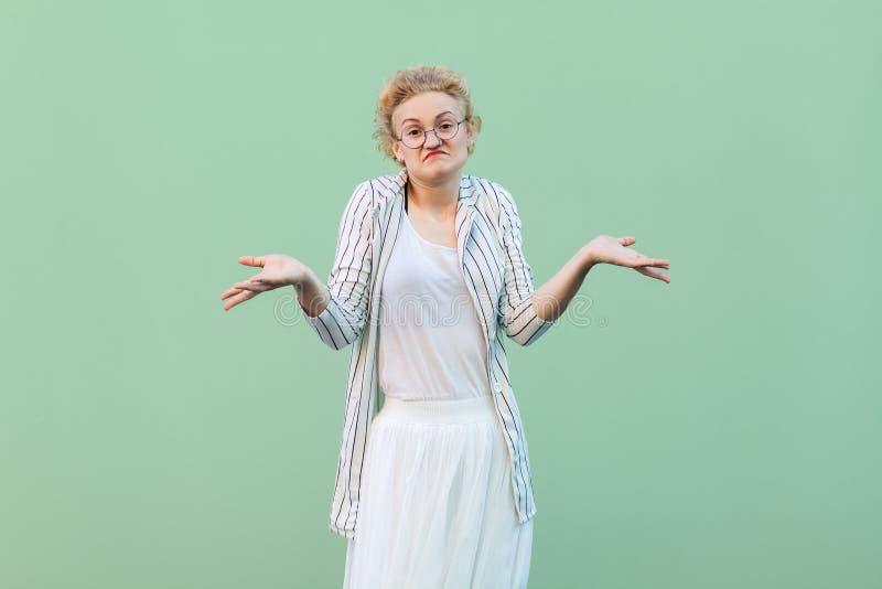 Ik trek `t het weet aan Portret van verwarde twijfelachtige jonge blondevrouw in witte gestreepte blouse met oogglazen die opgehe stock fotografie