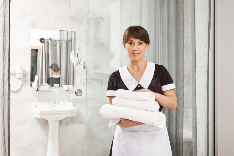 Ik verzeker u grote tijd in ons hotel zult hebben Portret van het prettige Kaukasische vrouw werken als dienstmeisje, het houden stock fotografie
