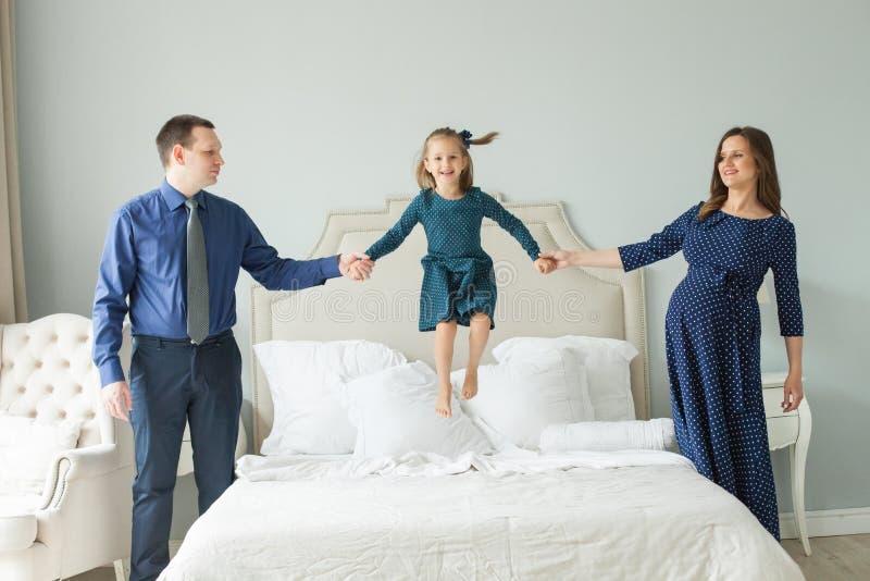 Ik vlieg! Gelukkige familie die op het bed springen royalty-vrije stock afbeelding