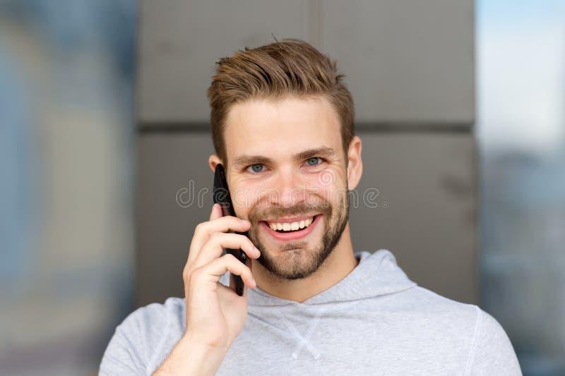 Ik wachtte op uw vraag Mensenbaard met smartphone, stedelijke achtergrond Communicatie concept Mens met gelukkige baard stock foto's