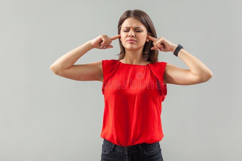 Ik wil je niet horen Portret van een verward brunette jonge vrouw in een rood hemd met gesloten ogen en met haar vinger stock foto