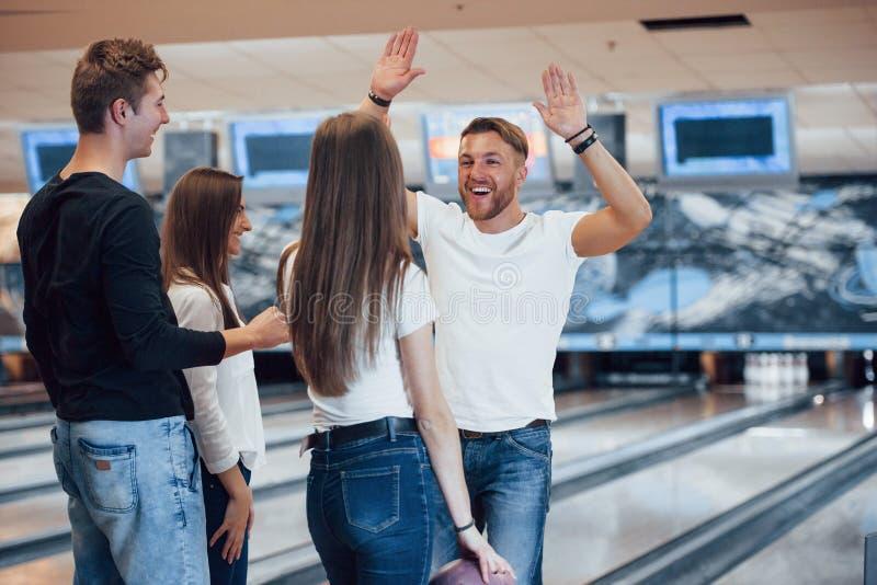 Ik wil je vijf. Jonge goede vrienden hebben plezier in bowlingclub in hun weekends royalty-vrije stock afbeelding