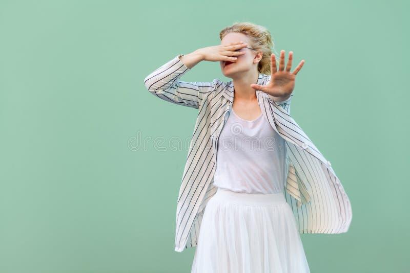 Ik wil niet dit bekijken Doen schrikken jonge blondevrouw in wit overhemd, rok, en gestreepte blouse status, die haar ogen behand stock foto