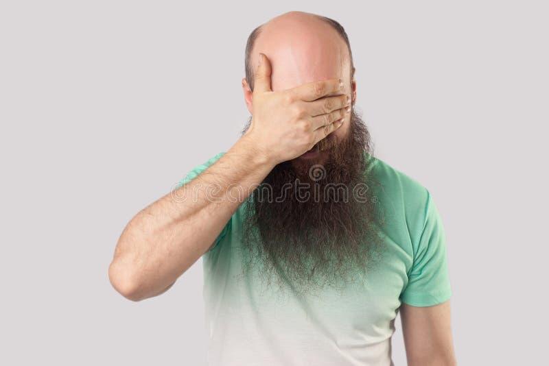 Ik wil niet dit bekijken Portret van de doen schrikken of geschokte midden oude kale mens met lange baard in lichtgroene t-shirt  stock afbeeldingen