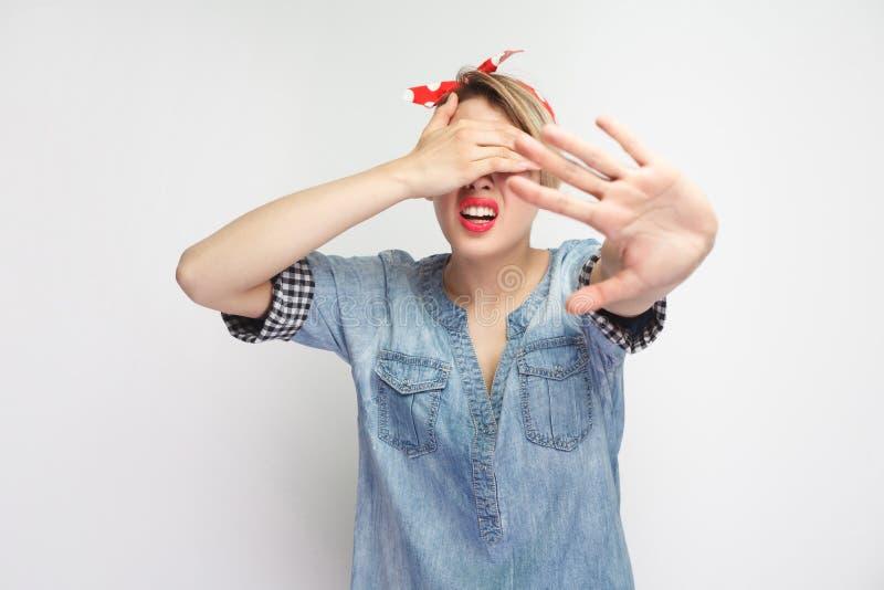 Ik wil niet dit zien Portret die van doen schrikken jonge vrouw in toevallig blauw denimoverhemd en rode hoofdband die, haar ogen stock foto's