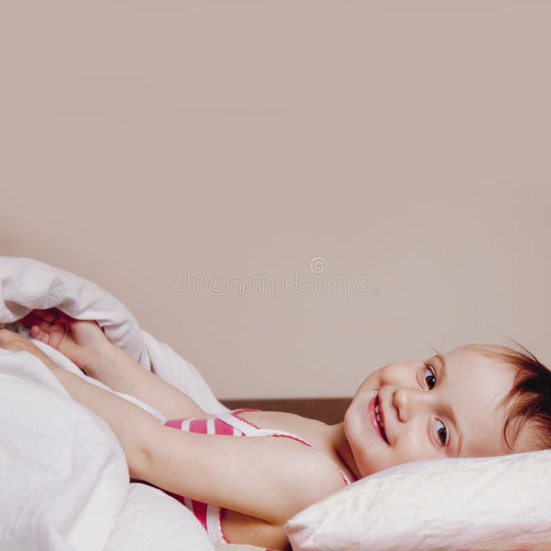 Ik wil niet nog slapen Het grappige leuke actieve meisje pret in bed hebben en doesn ` t die willen gaand in slaap vallen stock fotografie