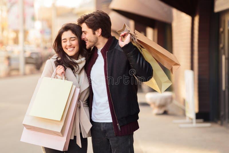 Ik zal het kopen Gelukkig paar met het winkelen zakken, man die aan vrouw fluisteren royalty-vrije stock afbeeldingen