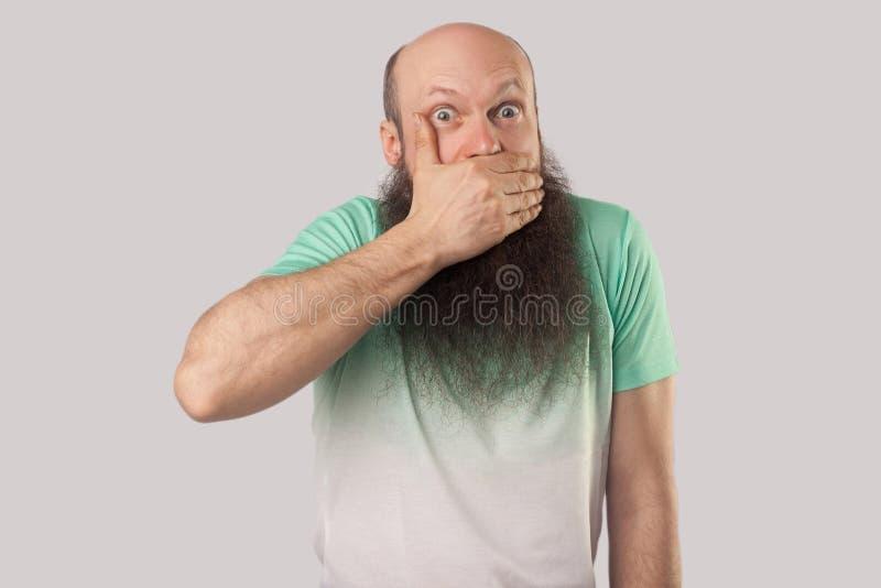 Ik zal stil zijn Portret die van de geschokte midden oude kale mens met lange baard in lichtgroene t-shirt die, zijn mond behande royalty-vrije stock afbeelding