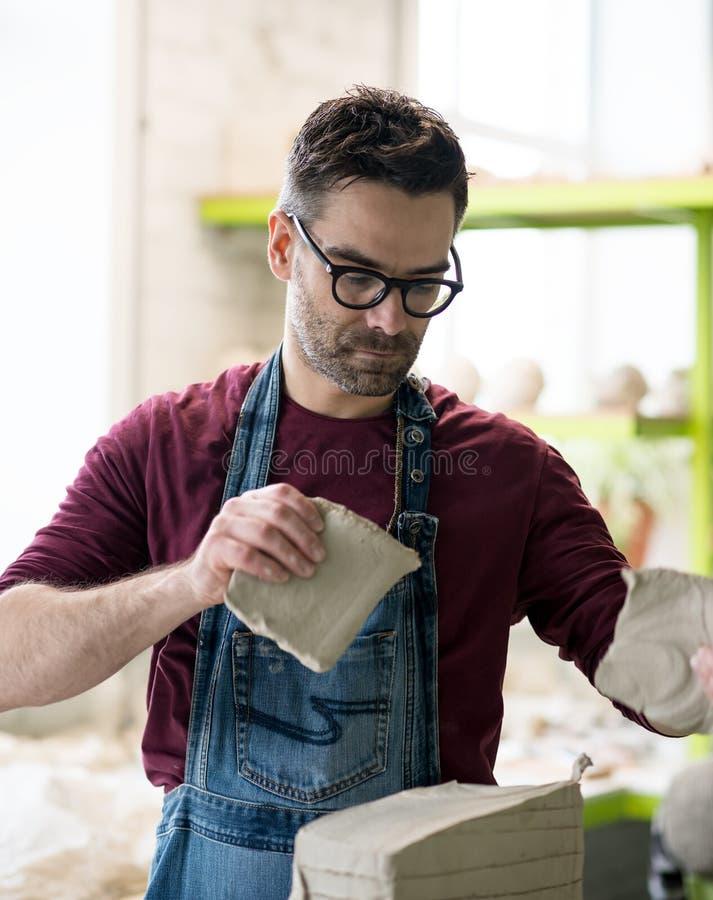 Iklädd Ceramist ett förkläde som arbetar med rå lera i ljust keramiskt seminarium royaltyfri foto