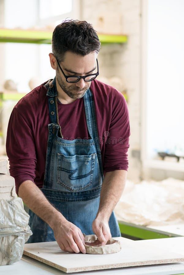 Iklädd Ceramist ett förkläde som arbetar med rå lera i ljust keramiskt seminarium royaltyfri fotografi