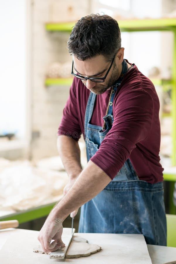 Iklädd Ceramist ett förkläde som arbetar med rå lera i ljust keramiskt seminarium fotografering för bildbyråer