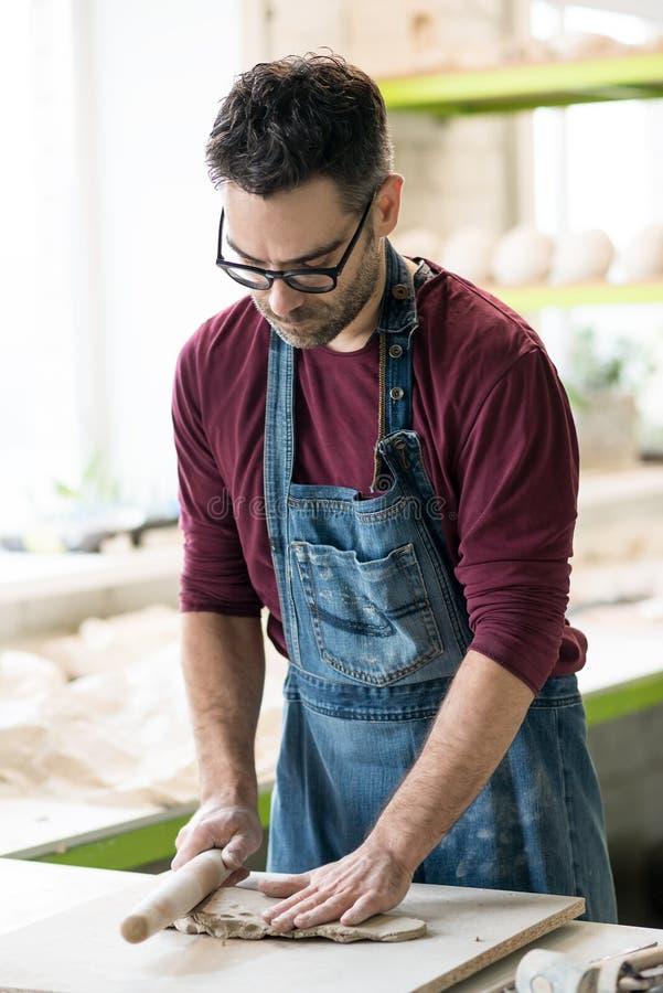 Iklädd Ceramist ett förkläde som arbetar med rå lera i ljust keramiskt seminarium arkivfoton